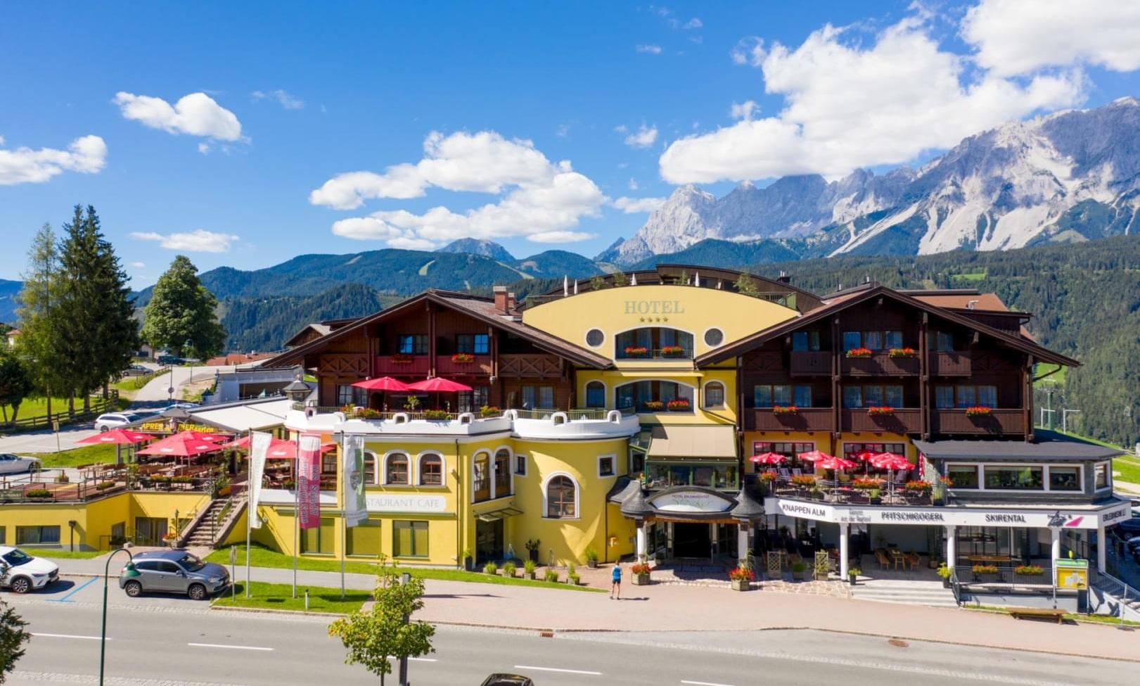 Sommerliche Hotelansicht Erlebniswelt mit Bergen im Hintergrund